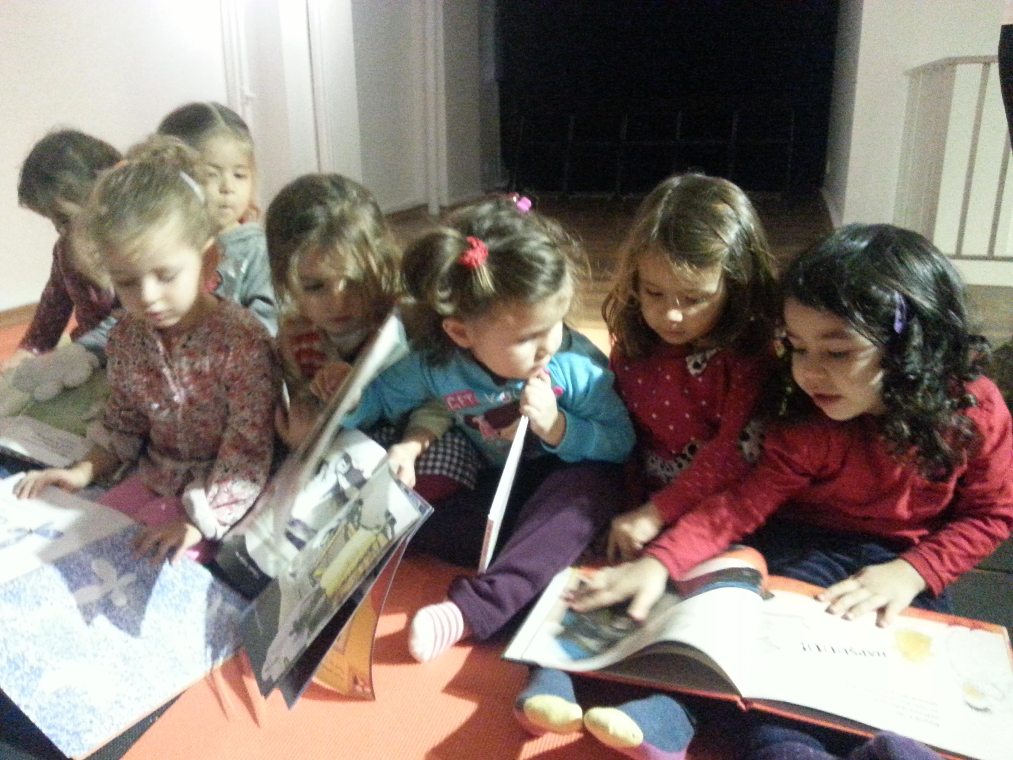 Çocuklar kitaplarını paylaşıp birlikte kitap okurken